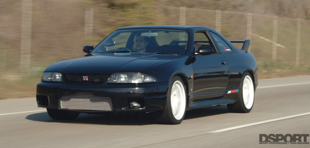 R33 Skyline driving on the street.